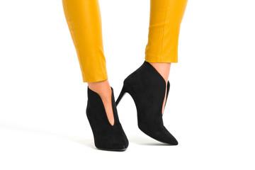 Kobiece nogi w butach na wysokom obcasie na białym tle