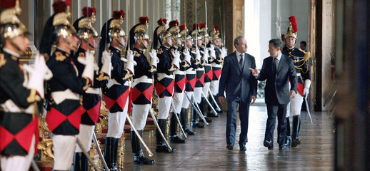 Paris Mayor Bertrand Delanoe walks with French President Nicolas Sarkozy at Paris city hall