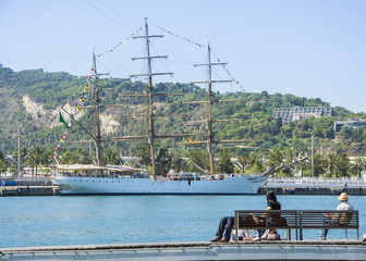 People resting and watching the sea on a sunny morning at Port Vell harbor in Barcelona