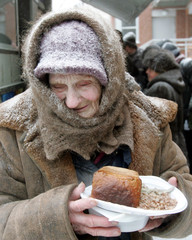 An elderly woman holds a plate of food she received at a distribution point for the homeless in Moscow