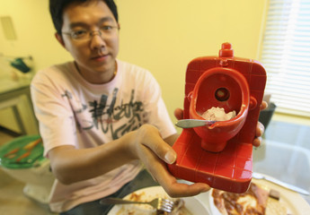 A diner shows an ice cream dessert inside a miniature toilet bowl at a toilet-themed restaurant in Hangzhou