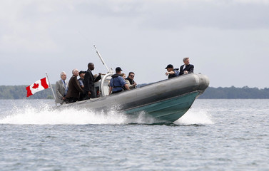 Canada's Prime Minister Stephen Harper rides a boat on his way to visit the HMCS Ville de Quebec frigate anchored in the bay of Port-of-Spain