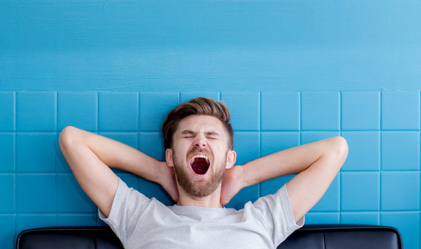 man yawning and going asleep in his  living room