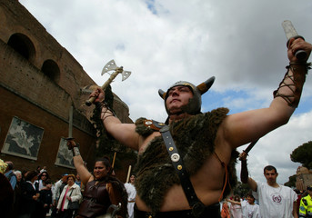 MEN DRESSED AS ANCIENT BARBARIANS MARCH THROUGH THE STREETS OF ROME.