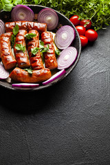 Grilled sausage, herbs and vegetables on black table
