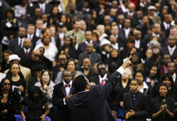 Singer Bobby Byrd points into the air while singing during a public viewing and funeral for legendary singer James Brown in Augusta