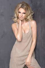 Sensual beautiful blonde woman over grey background