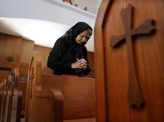 An elderly Iraqi woman prays for those killed in last week's bloody attacks while attending Sunday s..