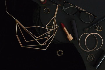 Flat lay of woman's accessories over the black background