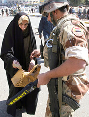 Iraqi soldier searches a woman's handbag at checkpoint in Baghdad.