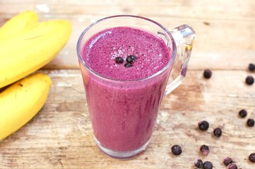 Healthy fresh smoothie drink from banana and blueberries in glass on wooden background