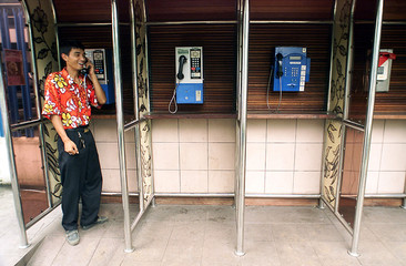 AN INDONESIAN MAN USES A PAYPHONE IN JAKARTA.