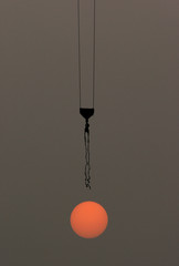 A crane passes above the setting sun on a construction site in Beijing