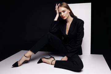 High fashion portrait of young elegant woman in black suit.