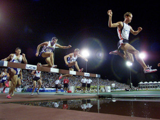 Pascal Dobert (R) clears the water hazzard during the men's 3000m steeplechase final at the U.S. Oly..