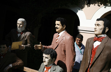 A journalist walks behind a life-sized statue of Honduras' ousted president Zelaya standing among statues of Honduras' founding fathers in Tegucigalpa