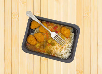Sweet and sour chicken TV dinner with a fork atop a wood place mat.