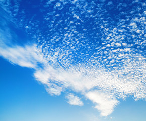 Blue sky with many fluffy white clouds. Natural background.