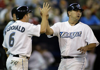 Blue Jays McDonald and Huckaby celebrate after scoring against the Devil Rays.