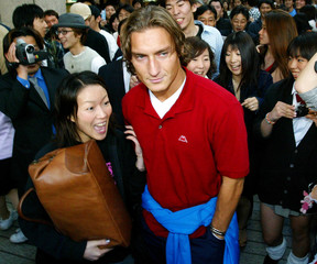 ITALY'S FRANCESCO TOTTI IS SURROUNDED BY FANS IN CENTRAL SENDAI.