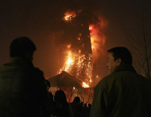 A crowd watch as the building that housed the to-be-opened Mandarin Oriental Hotel explodes after it caught on fire in Beijing