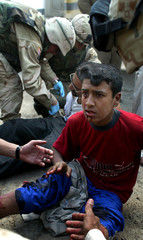 INJURED IRAQI BOY RECEIVES MEDICAL ATTENTION AFTER STEPPING ONEXPLOSIVE DEVICE IN TAJI.
