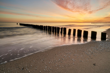 Beautiful sandy beach, baltic with a wooden breakwater