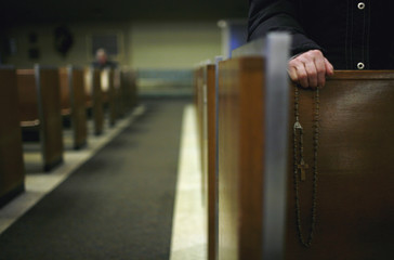 A parishioner holds her rosary beads as she prays at Immaculate Conception Catholic Church in Chicago