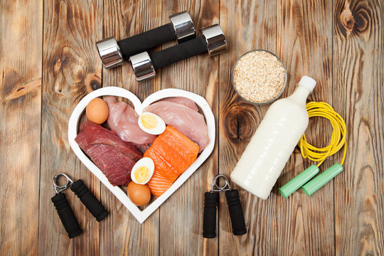 Proteins and dumbbells. Fish, cheese, eggs, meat, chicken  heart on wooden background
