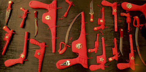Picture shows pistols, guns, grenades and other military accessories made of a soft fabric, filled with wool and decorated with beads and Soviet symbols