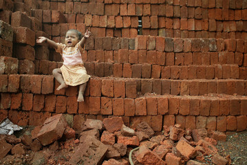 Indian girl cries for her mother who works at a building construction site in Mumbai.