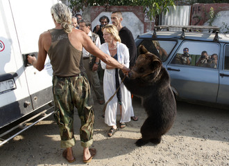 Bear trainer Mircea Molnar and his wife Dana hold Baloo, a three-year-old brown bear, before handing him to the authorities in Pantelimon village