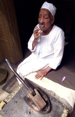 AN EGYPTIAN LEG IRONER TAKES A BREAK DURING IRONING IN HIS SHOP INCAIRO.