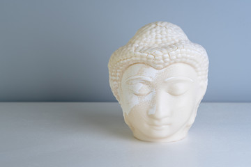Buddha face. Buddha statue made of white marble with free space for text. Concept of peace, calm and tranquility. Buddhist artifact for Zen style interior decor.