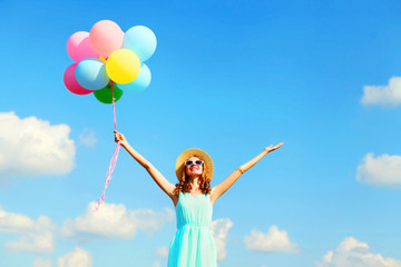 Happy young smiling woman with an air colorful balloons is enjoying a summer day over blue sky background