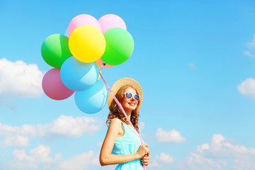 Happy young smiling woman with an air colorful balloons is having fun wearing a summer straw hat on a blue sky background