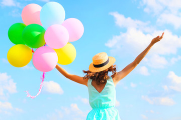 Lifestyle photo happy woman with an air colorful balloons is enjoying a summer day on a blue sky background