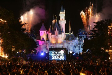Thousands of visitors gather as '2006' is displayed on a screen when the clock strikes twelve at Hong Kong Disneyland