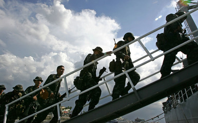 Members of the Philippine marines from the 1st Marine Battalion board an LST navy ship at the ...
