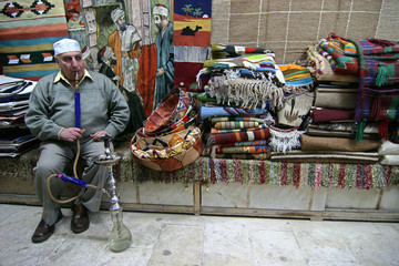 Hosni Muhammed, a tailor, takes a break to smoke sheesha in his shop in the tentmakers market in Cairo