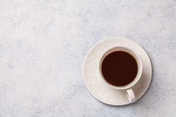 Black coffee in a white cup on a gray background