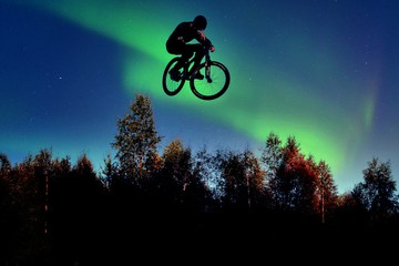 Low Angle View Of Man In Mid-Air Stunt With Bicycle Against Aurora Borealis