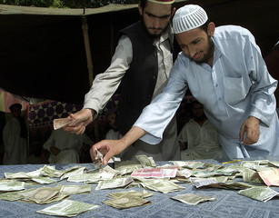 PAKISTANI MUSLIMS COLLECT RUPEES FOR A PRO-TALIBAN FUND IN FRONT OF THERED MOSQUE IN ISLAMABAD.