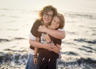 mother hugs a blonde kid in a beach