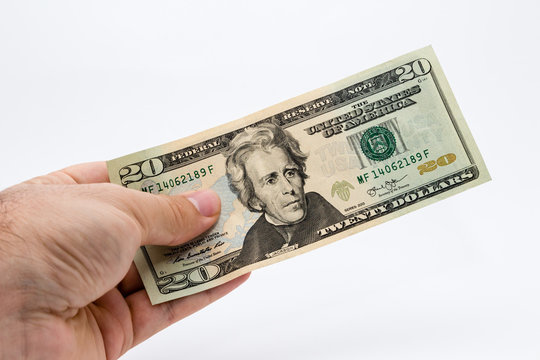 a close up photo of a Caucasian male hand holding a 20 dollar USA note