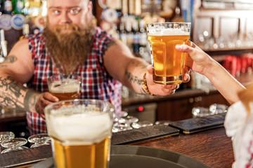 Fat bartender holding beer in arm