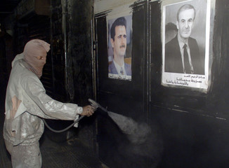 SYRIAN WORKER SPRAYS THE WALL IN BLACK IN ALL OF THE SHOPS IN QARDAHA VILLAGE.