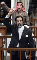 Former Iraqi president Saddam and former intelligence chief Barzan berate the court during trial in Baghdad