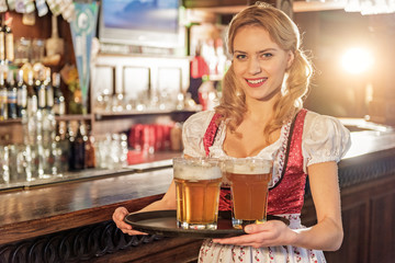 Cheerful woman holding tray with beer glasses