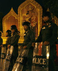 A portrait of Thai King Adulyadej is seen in the background as policemen in riot gear stand guard near the Government House in Bangkok